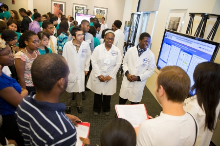 Genomics program students Eduardo Plascencia of Chicago, IL, Ja'Naysha Hamilton of Detroit, MI, Stephone Christian of Port Saint Lucie, FL (center, from left), and Erika Banuelos of Phoenix, AZ (bottom right) present their research on human micro-biomes. The students learned about the bacteria inhabiting the human body through hands-on experiments.