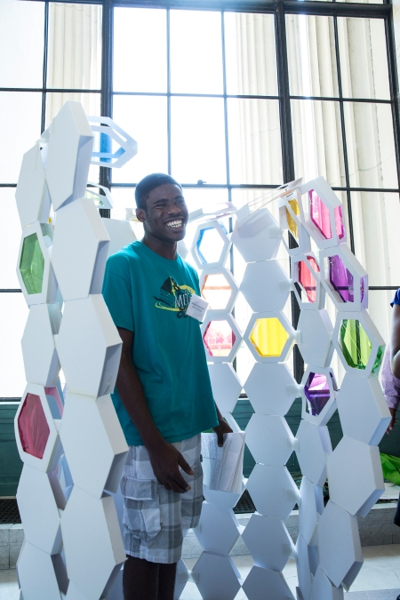 "Engineering Design program student Jeremiah Akinsulire of Jamaica, NY steps into ""The Busy Bee,"" a model phone booth made by Architecture program students Jennah Jones of Chapel Hill, NC, Carlos Romero of Boston, MA, Emanuel Perez of Chicago, IL and Diondra Dilworth of Las Vegas, NV."