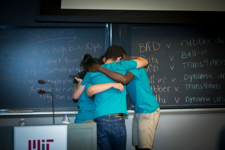 An Engineering Design team huddles before resuming competition in the final Symposium game.