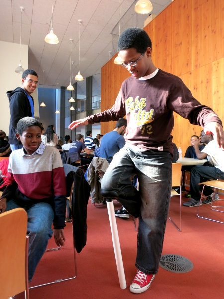A plunger wedged inside of a piece of PVC pipe supports the weight of mentoring student George King III. Teammate Isaah Adedeji (seated) and mentor Chris Kelley – a MITES '09 alum – observe the test of an early model prosthetic leg.