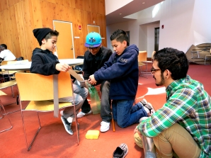 Under the supervision of mentee Roandy Herrera (center) and mentor Douglas Sanchez mentee (right), Joel Aguila stretches out a piece of duct tape for teammate Kevin Vazquez to cut. The team's design would lead them to become co-champions of the design challenge.