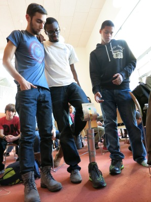 Co-champion teammate and mentee Miles Graham explains the tilting knee holding mechanism on the prosthesis demoed by mentor Jide Akinrunbi with support from mentor Andrew Berta.