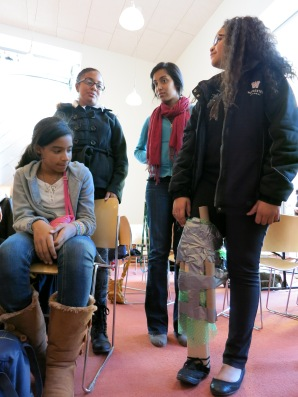 Mentees Leah Delacruz and Kyara Gonzalez explain the merits of their prosthesis's bulkier top as mentor Tahoura Samad observes and mentee Victoria Andrews models.