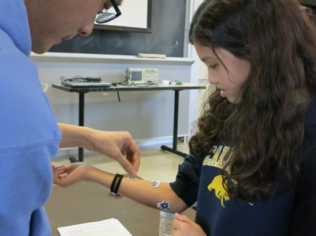 On April 5, OEOP Middle School Mentoring Program participants, including Kiana Fields (right), stuck electrodes to their arms to observe the power of the electrical signals that travel through their muscles.