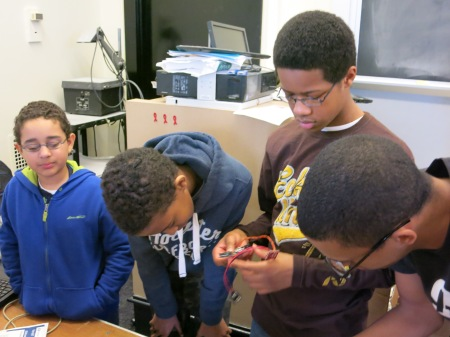 Part of the activity charged students to build systems that allowed them to control a single motor with electrical signals from their muscles. Mahamud Hashi (second from left) reviews instructions while George King II (second from right) inspects the materials.