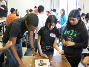 MIT undergraduates Chris Kelly (left) and Sharin Islam (right) help middle school student Belkis Vergara navigate the instructions to properly connect wires to the electrodes on her arms.