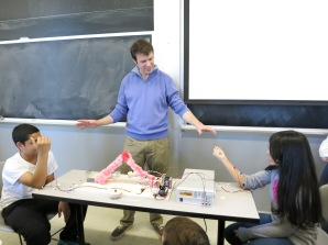 MIT Professor Joel Voldman (center) moderates a WrestleBrainia match – in which students controlled mechanical arms using the electrical signals generated by their muscles – between Anthony Romero (left) and Daniela Reyes (right).