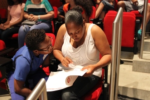 Clyde Jefferson and his mother flip through the family handbook during orientation on Wednesday, July 2 in the Ray and Maria Stata Center at MIT. During the orientation, families prepared for the program and met the instructors and staff.