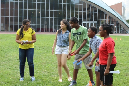 As part of the Math Olympics for their level three probability and statistics course, Kathryn Miranda, Shirley Cheung, Calvin Hill, Dennis Mullings, and Angelique Jean-Noel (left to right) toss horseshoes before completing math problems.