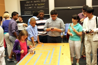 Level four student Luis Franco (center) test drives his final robotics project at the 2014 STEM Sumer Institute Final Ceremony as level one student Kevin Matos (second from left) and other STEM Program family members look on.