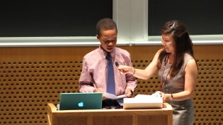 Lead academic advisor Catherine Park (right) introduces level two student Rhocar Constant before his speech at the 2014 STEM Summer Institute Final Ceremony. Each level elected a student speaker to represent their class to tell family members and friends about their experience with the STEM Program this summer.